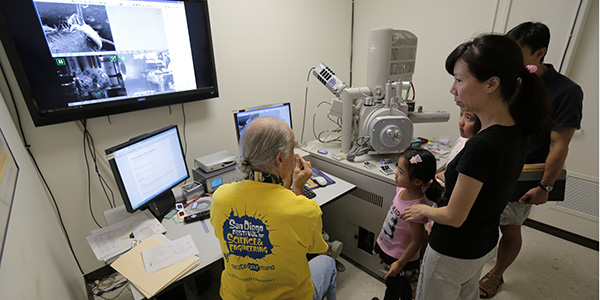 Richard Bizzoco demonstrating microcope to a family